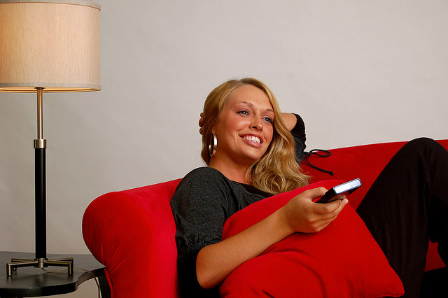 Woman using an electric fireplace remote from the couch
