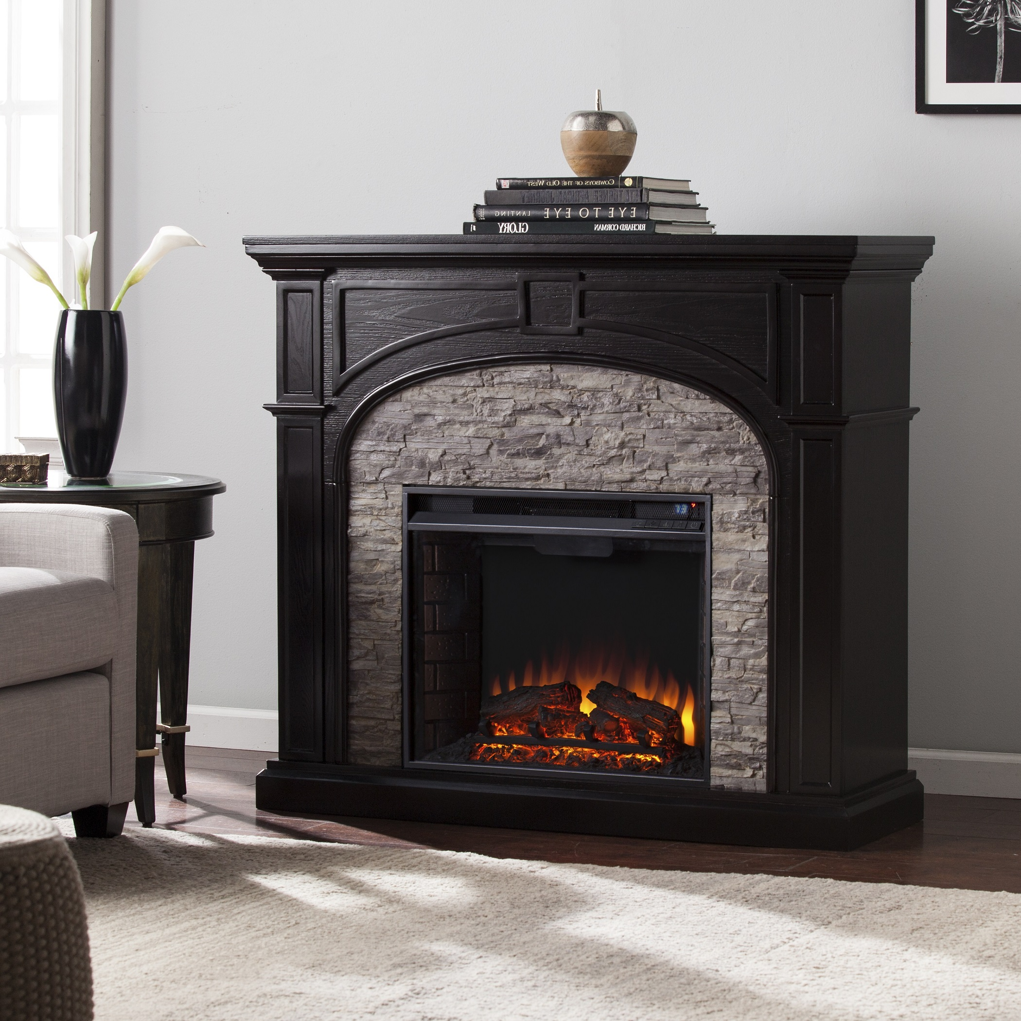 Ignite your senses with this updated lodge style electric fireplace. Rich ebony finish arches over the realistic gray faux stone surround.